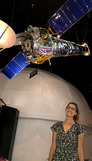 Adi Foord standing beneath a model of the Chandra X-ray Observatory