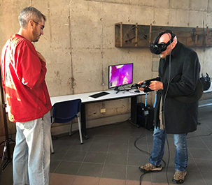 Image of Nobel Laureate Prof. Kip Thorne exploring the the VR app, assisted by Dr. Christopher Russell.